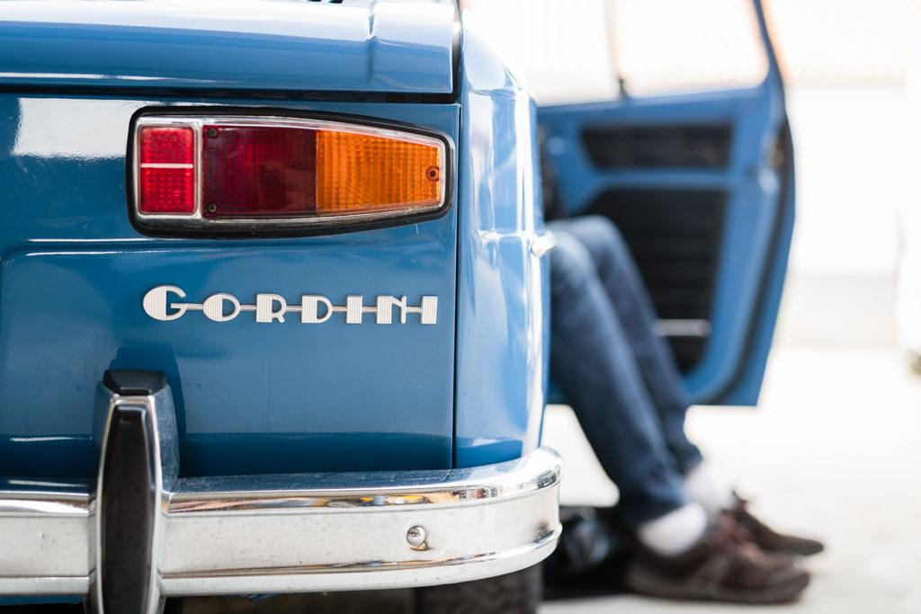 feu arrière d'une R8 gordini bleue, avec une personne en jean dont les jambes dépassent côté passager.