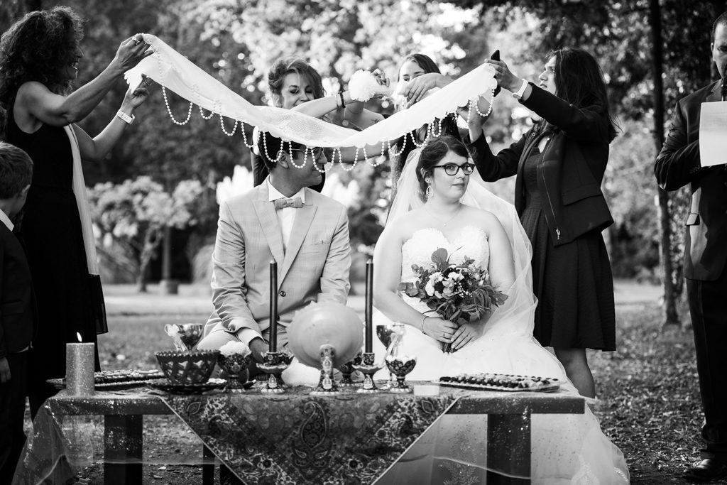 Couple assis devant une table de cérémonie, surplombé par un tissu orné de perles par-dessus lequel une invitée frotte deux morceaux de sucre l'un sur l'autre