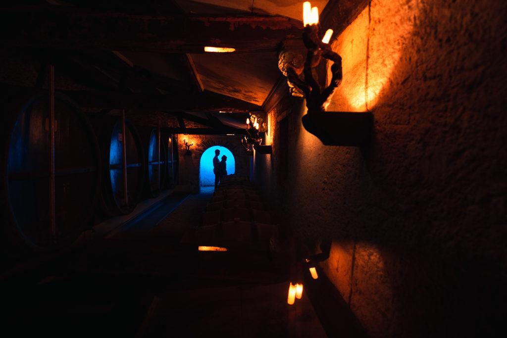 photo de couple au chateau de la cassemichère en ombres se détachant dans un chai avec jeu de couleurs bleue et jaunes