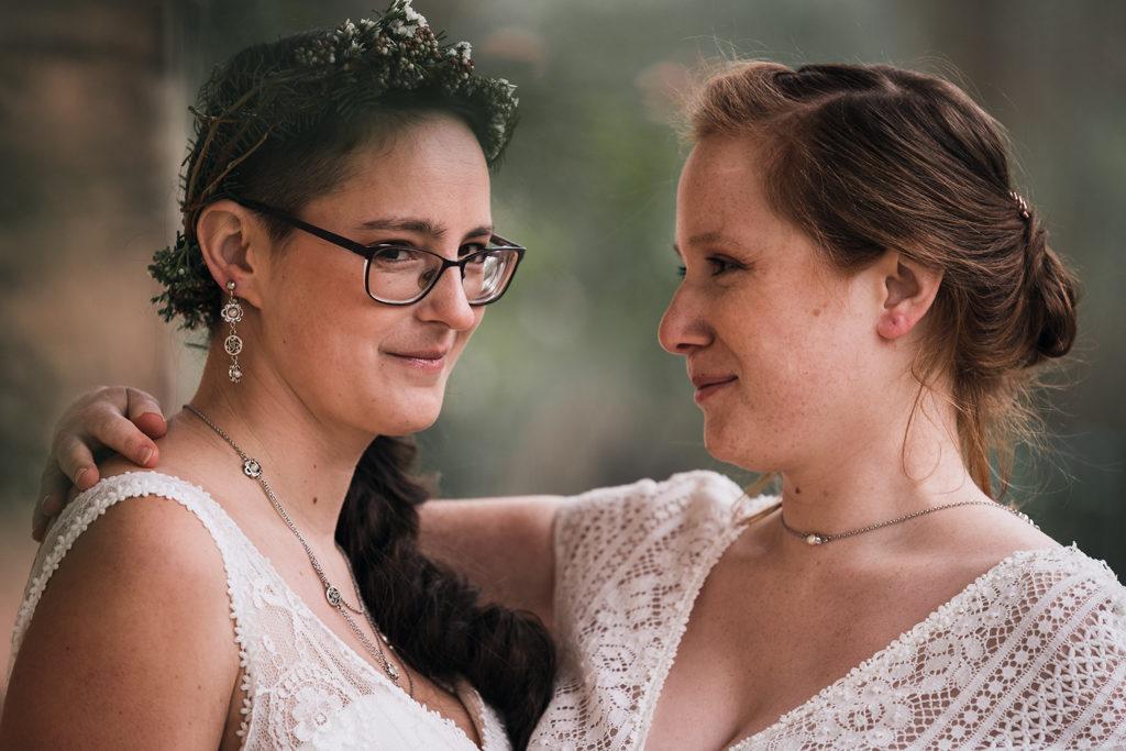 Photo d'un couple de femmes, celle de gauche regarde l'objectif, celle de droite regarde celle de gauche