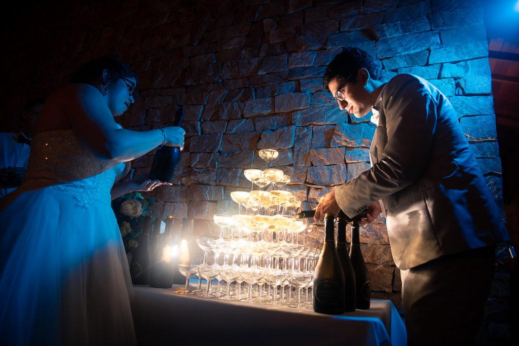 Couple de mariés versant le champagne sur une fontaine de champagne