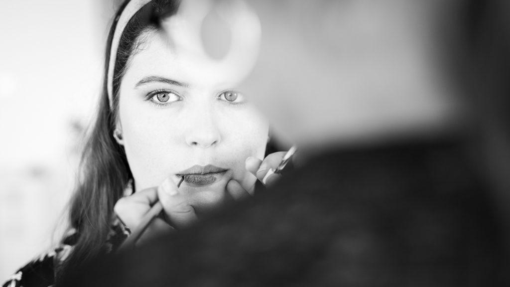 mise en beauté de la mariée vue de face. La maquilleuse applique le rouge à lèvres
