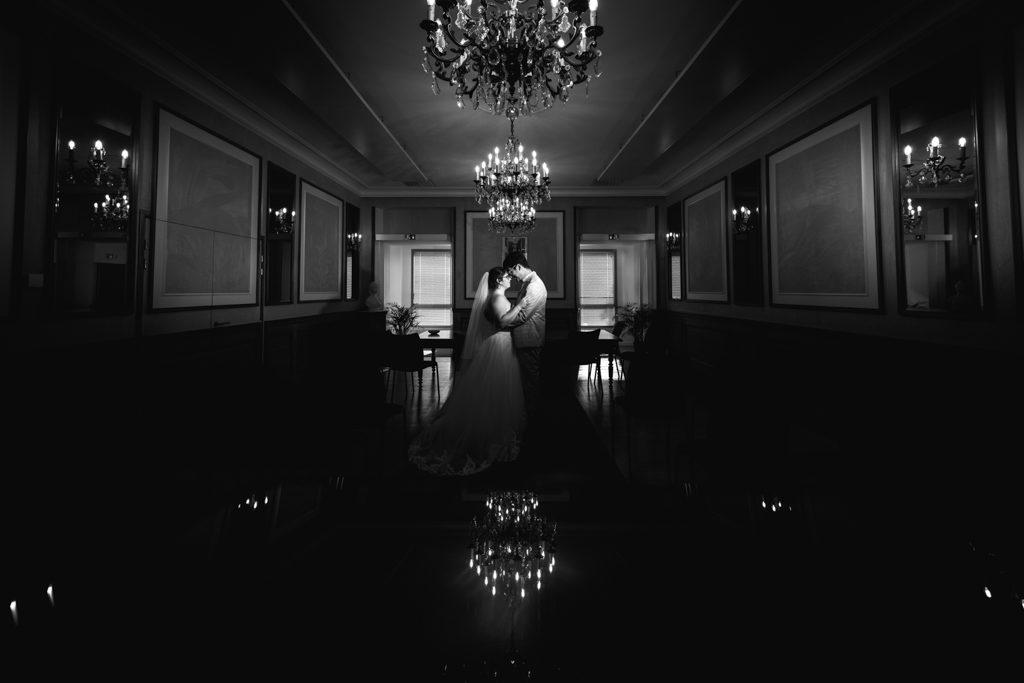 Un couple se tient face-à-face au centre de l'image, sous un chandelier.