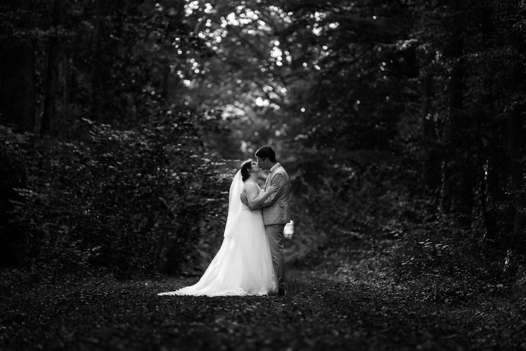 Couple de mariés s'embrassant sous les arbres