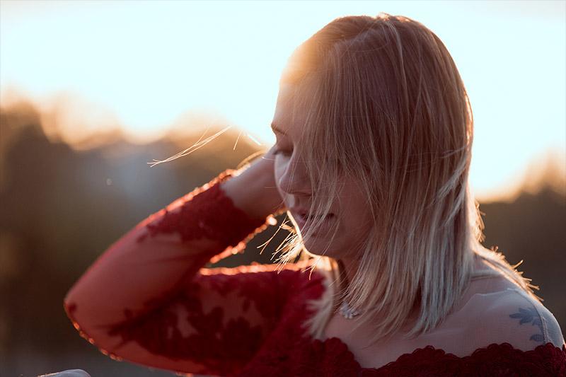 jeune femme blonde avec une robe rouge à l'heure dorée