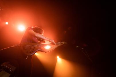 Photographie d'un bassiste pendant un concert, vu en contre-plongée avec des jeux de lumière rouges