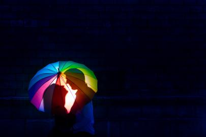 Photographie d'un couple sous un parapluie multi-colore, leurs ombres face à face se détachent sur le parapluie