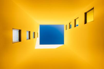 bâtiment jaune à Bordeaux en contre-plongée avec des lignes de fuites formées de fenêtres menant vers un carré de ciel bleu