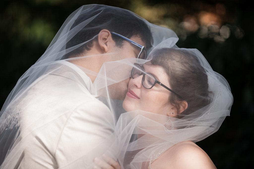 couple sous un voile de mariée, le marié embrassant la mariée qui a les yeux fermés