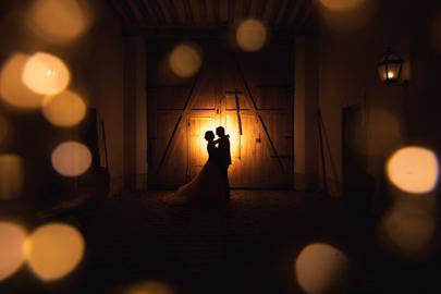 photographie de mariage d'un couple dont l'ombre se détache sur un cercle de lumière projeté sur une porte en bois, avec des lumières scintillants au premier plan