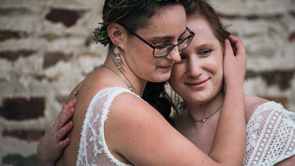 Couple de mariées dans les bras l'une de l'autre
