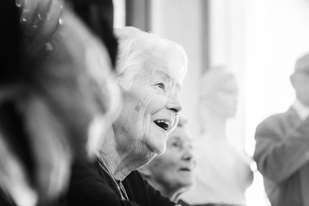 Grand-mère en train d'assister au mariage, le sourire jusqu'aux oreilles