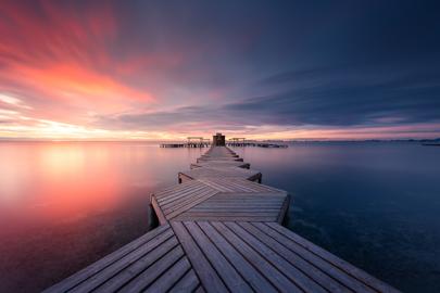 Ponton sur la mer au lever de soleil en Espagne, le ciel est rose à gauche de l'image et devient bleu à droite de l'image