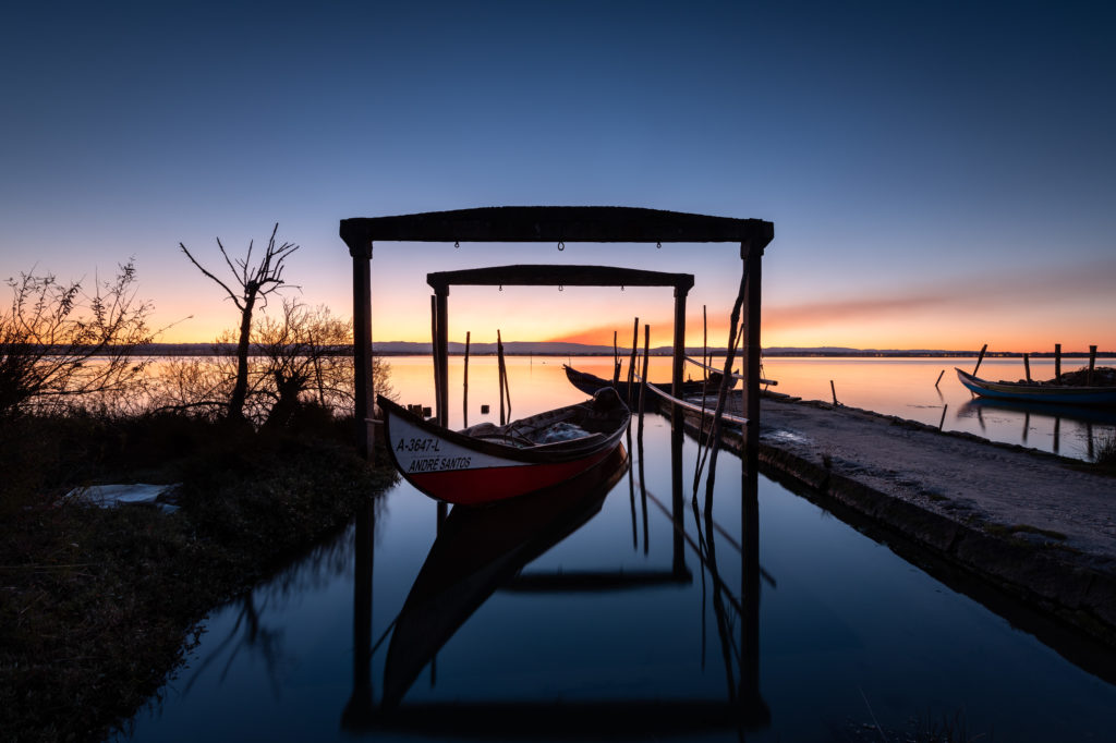 barques portugaises au petit matin avec des portiques en bois formant un cadre se reflétant dans l'eau