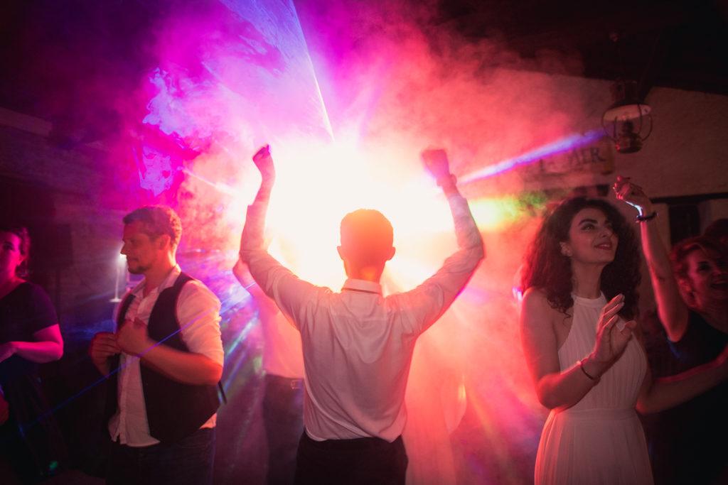 Personne de dos, dansant les bras levé, avec des lumières formant un halo autour de lui