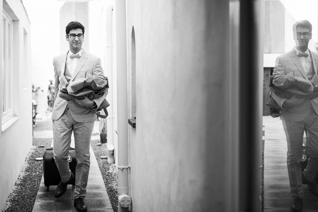marié en tenue, affaires et valise en main, sortant du lieu de ses préparatifs. On aperçoit son reflet dans une vitre