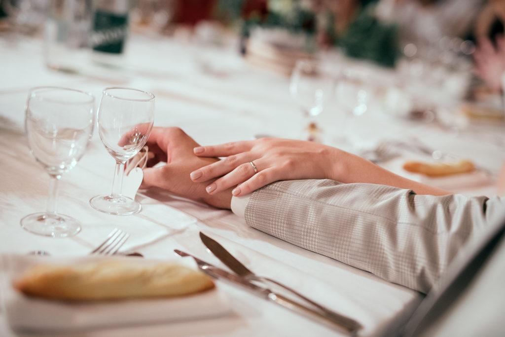 détail des mains des mariés pendant le repas. La main de la mariée, avec l'alliance, est posée sur celle de son mari.