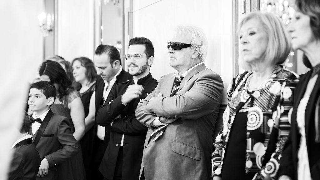 invités à un mariage lors de la cérémonie civile. L'un d'eux porte des lunettes de soleil