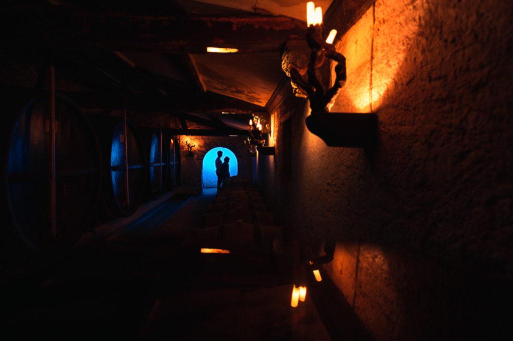 Photo de mariage d'un couple se détache au loin en ombres chinoises dans une voute éclairée en bleu. Au premier plan on devine un chai, éclairé par des lumières chaudes orangées.