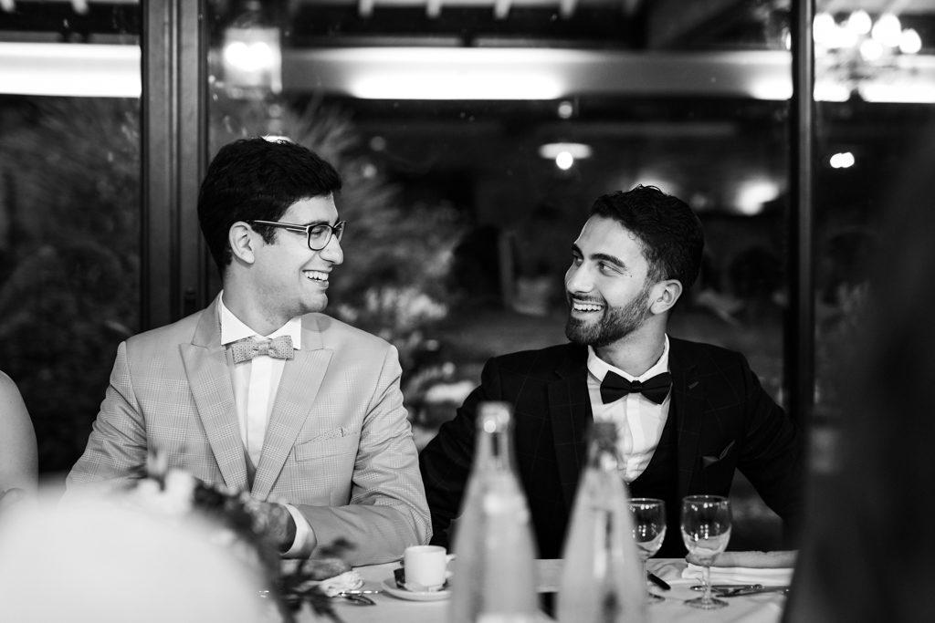 un marié et son témoin discutant en souriant à la table d'honneur