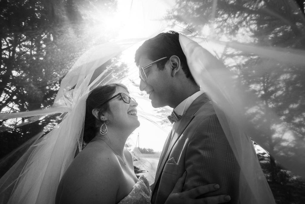 couple de mariés se regardant dans les yeux, prise sous le voile