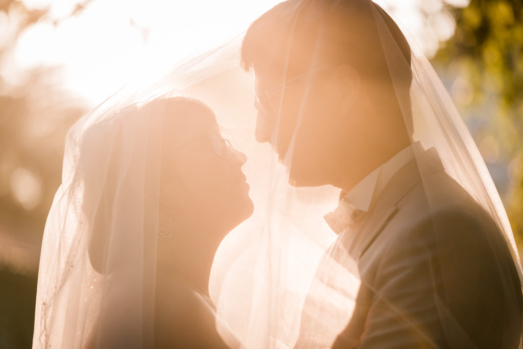 Couple se regardant dans les yeux sous un voile de mariée à l'heure dorée