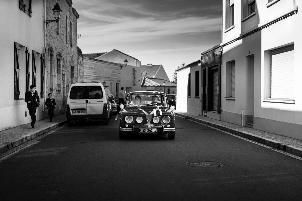 voiture des mariés de face, roulant vers nous, avec sur le trottoir des enfants qui courent en regardant la voiture