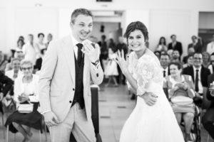 le couple montre les alliances en souriant, juste après les avoir passées