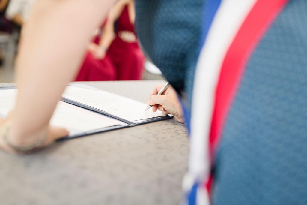 Moment de la signature pendant un mariage à Brie-Comte-Robert en Ile-de-France. L'employée de mairie est en train de signer le registre