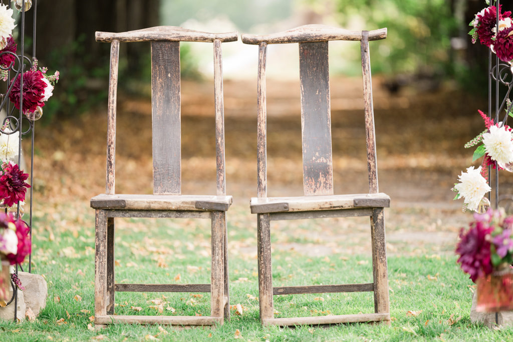 Chaises des mariés, placées sous une arche fleurie au domaine de quincampoix