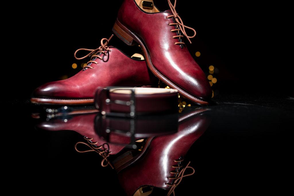 accessoires du marié, chaussures et ceinture, se reflétant sur un bureau