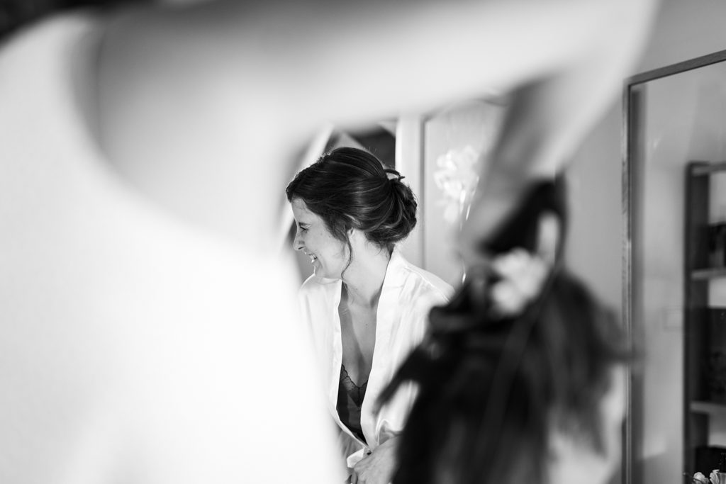 Mariée riant aux éclats pendant la coiffure de sa maman