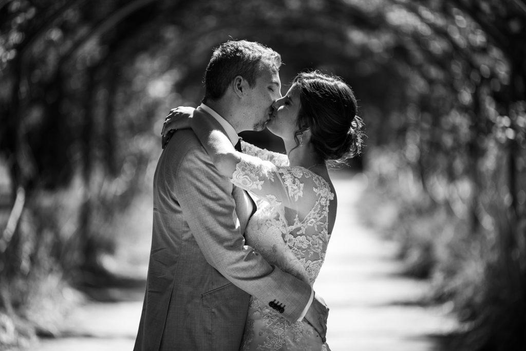 Couple s'embrassant sous une allée d'arbres, photo en noir et blanc, cadré sur les bustes