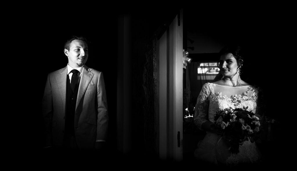 Couple de futurs mariés dans leurs tenues, avant qu'ils ne se découvrent. Ils se tiennent chacun dans l'encadrement d'une porte et regardent dans la direction l'un de l'autre