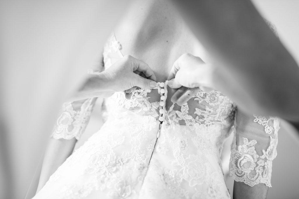 mariée pendant son habillage, les mains accrochent les boutons de la robe un par un