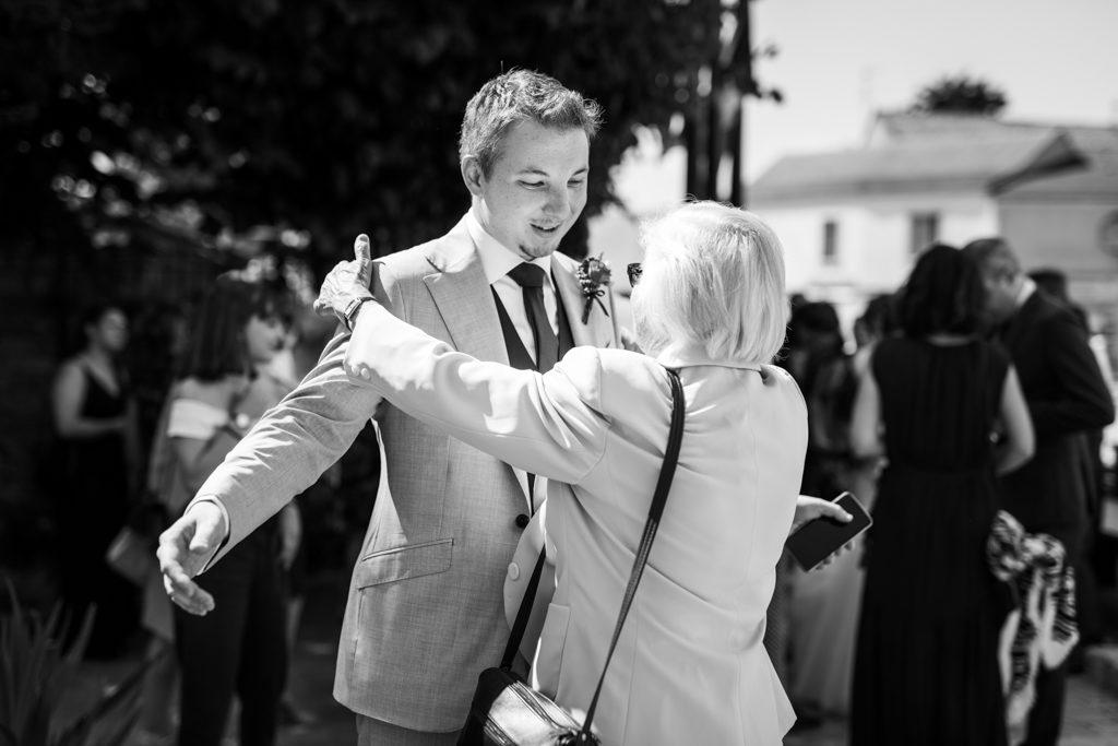 Marié prenant l'une des invitées dans ses bras avant l'entrée dans la mairie