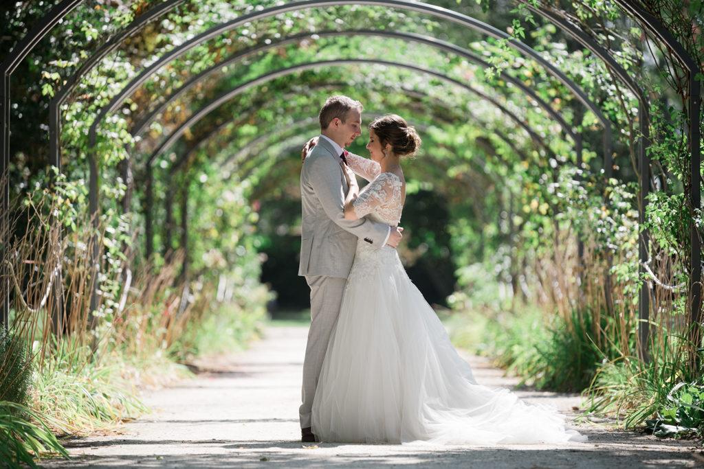 couple s'embrassant sous une allée végétale