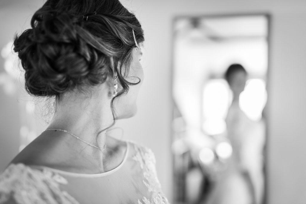 Mariée s'admirant dans le miroir, la mise au point est faite sur la coiffure