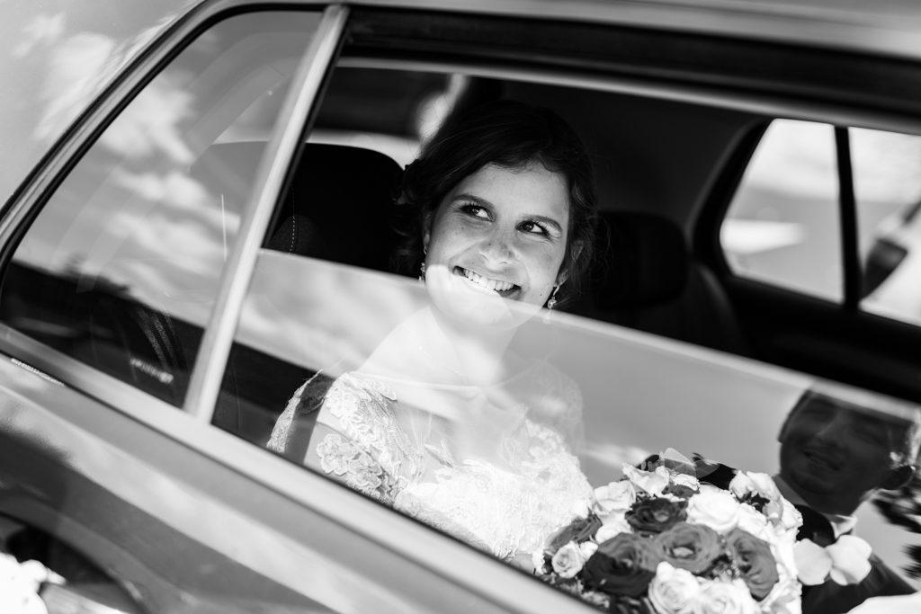 La mariée regardant son mari depuis l'intérieur de la voiture, et le marié se reflétant dans la vitre de la voiture