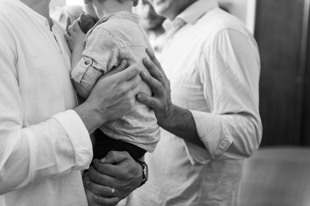 Le marié et son fils, une main se pose sur le dos du petit