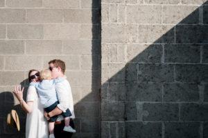 triangles de lumière naturels sur un mur de briques. Le couple tient leur enfant dans leurs bras, et un chapeau est en train de tomber