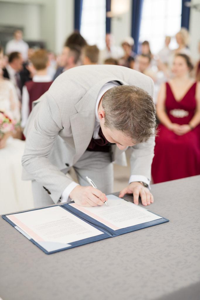 le marié signant le registre à la mairie