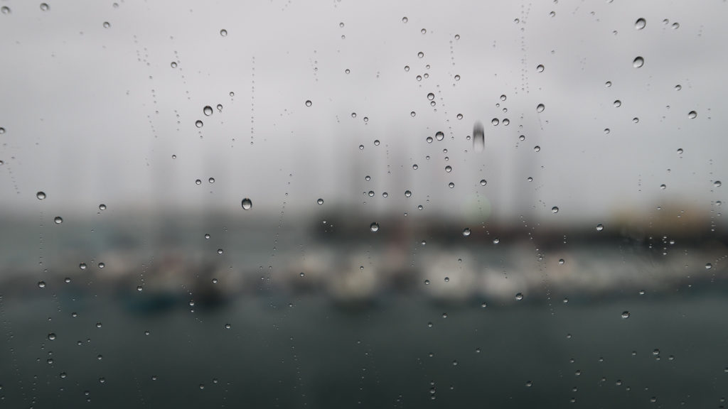 rain drops on a window. we can guess the boats in reykjavik through the glass