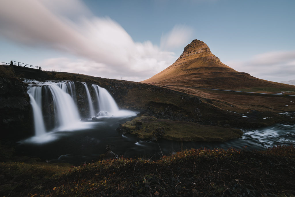 kirkjufellsfoss, in iceland. We see the waterfall and a small mountain in the background