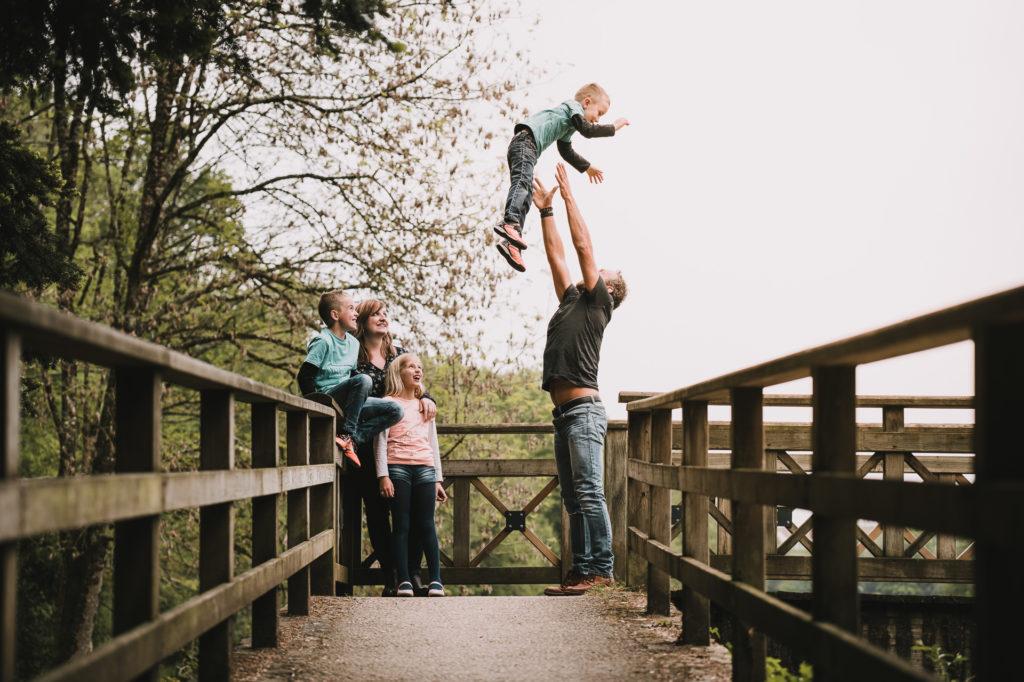 photo de famille lifestyle, un papa lance le petit dernier en l'air pendant que la maman et les deux enfants les regardent