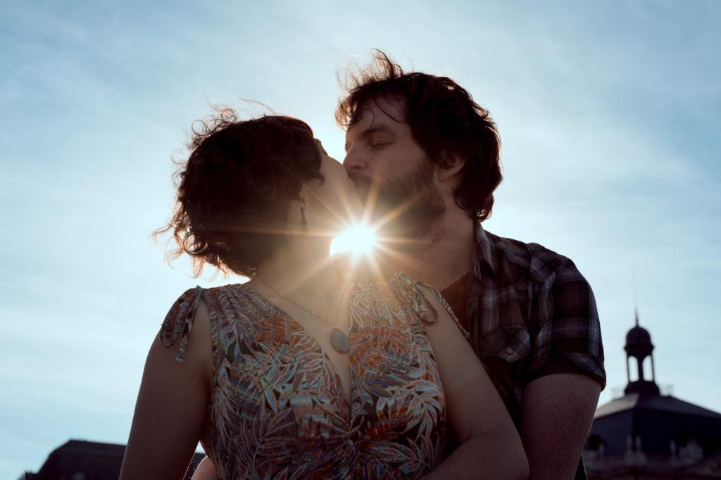 Photo de couple lifestyle, un couple s'embrasse, à contre-jour, avec le soleil