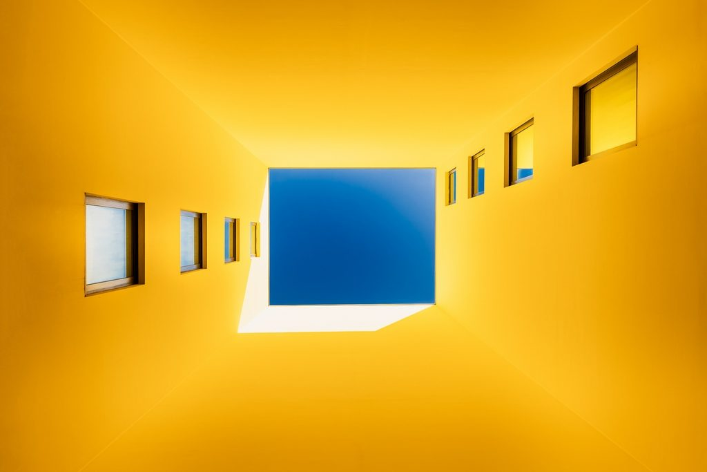 Bâtiment jaune en contre-plongée avec un carré de ciel bleu se détachant au centre de l'image