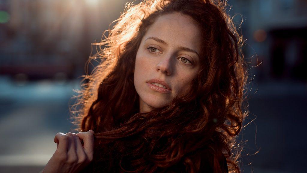 photo d'une jeune femme rousse à l'heure dorée, tenant une mèche de ses cheveux