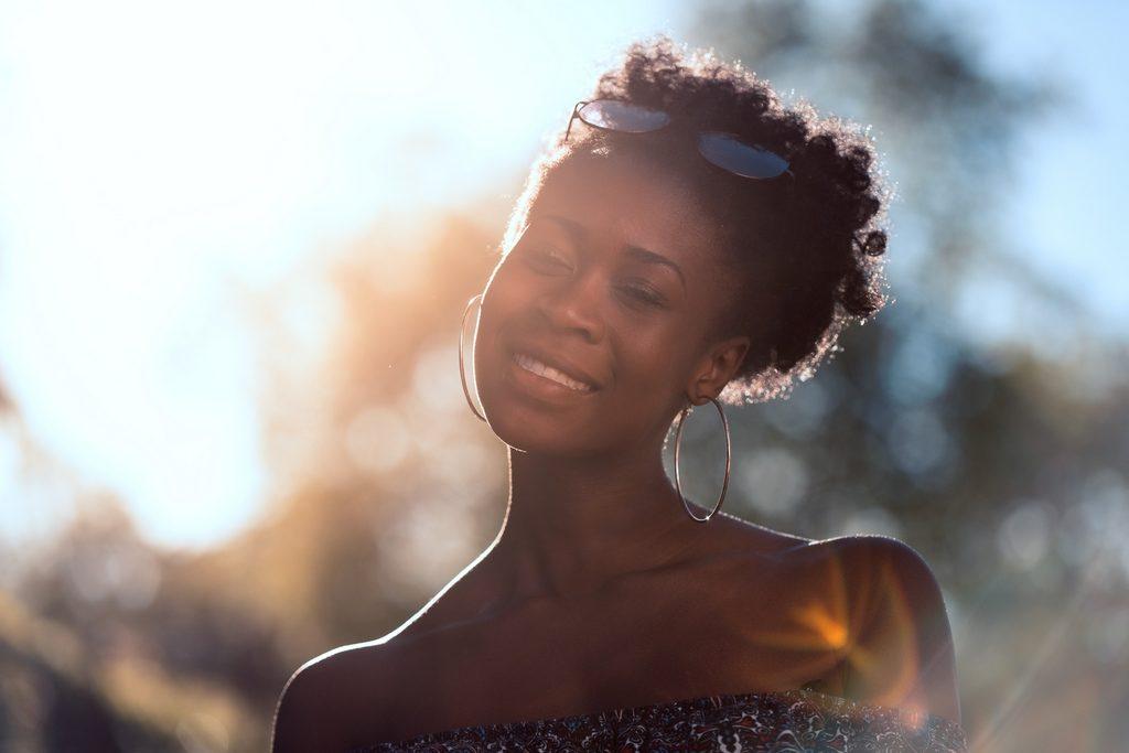 photo d'une jeune femme à la peau noire prise à l'heure dorée