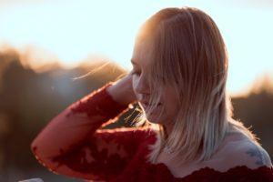 photo d'une jeune femme blonde avec une robe rouge, prise à l'heure dorée